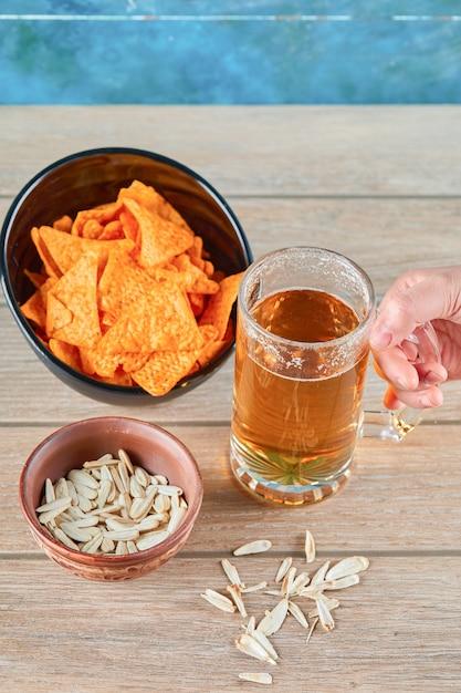 ヒマワリの種、チップスのボウル、木製のテーブルにビールのグラス。 無料写真