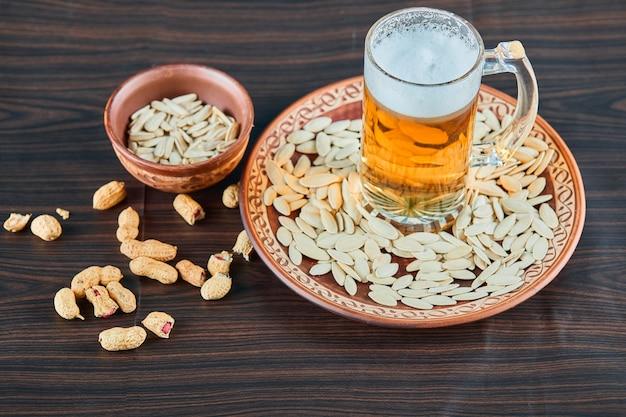 木製のテーブルにひまわりの種、ピーナッツ、ビールのグラス。 無料写真