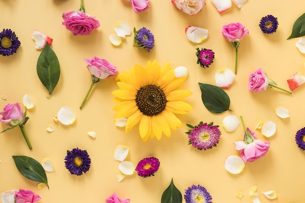 Sunflower surrounded with different types of flowers on yellow background Free Photo