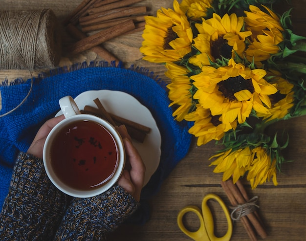 Sunflowers and a cup of hot tea holed by a girl Free Photo