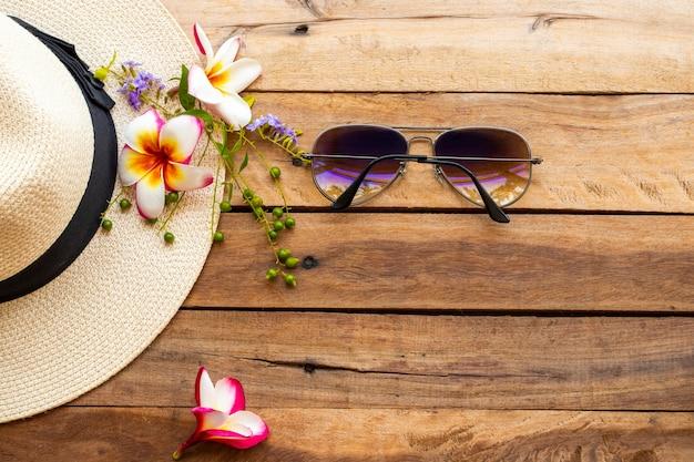 木製の背景に花とサングラスと帽子 Premium写真