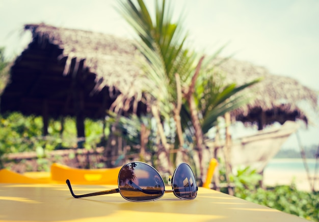 Sunglasses lying on a yellow table in a tropical beach cafe Premium Photo