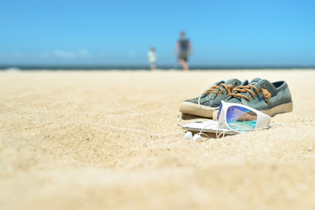 f787c5ab24fc62 Sunglasses and shoes on the beach with people on background Premium Photo