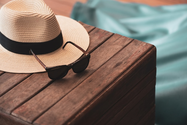 Sunglasses and straw hat on the wooden floor at the beach, summer concept. Premium Photo