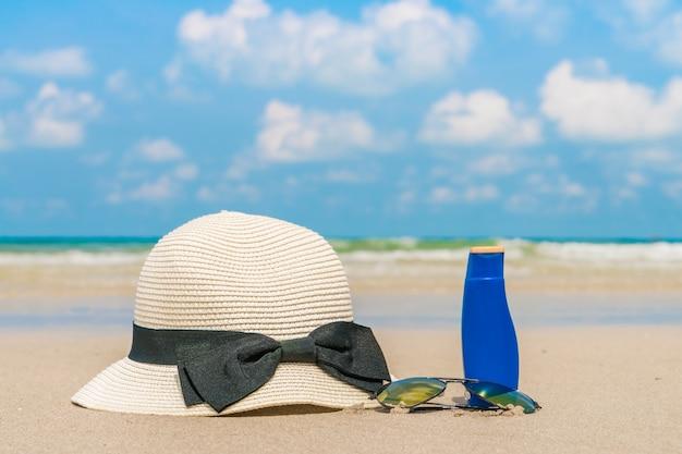 Sunglasses, sun cream and hat  on white  sand beach Free Photo
