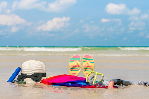 Sunglasses, sun cream and hat  on white  sand beach Free Photo