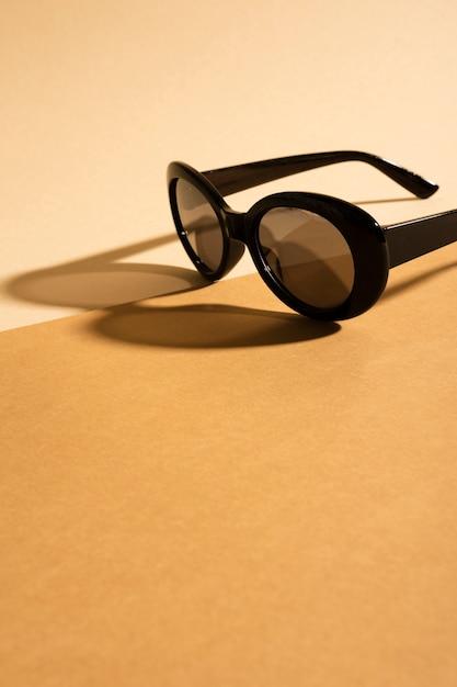 Occhiali da sole su un tavolo con ombra Foto Gratuite