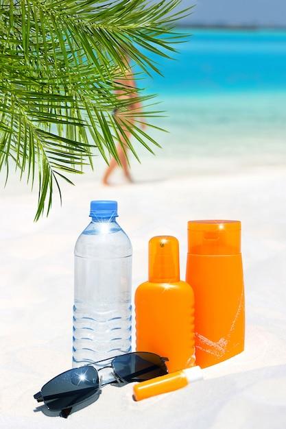 Sunglasses, water and sun protection cream on the beach Premium Photo