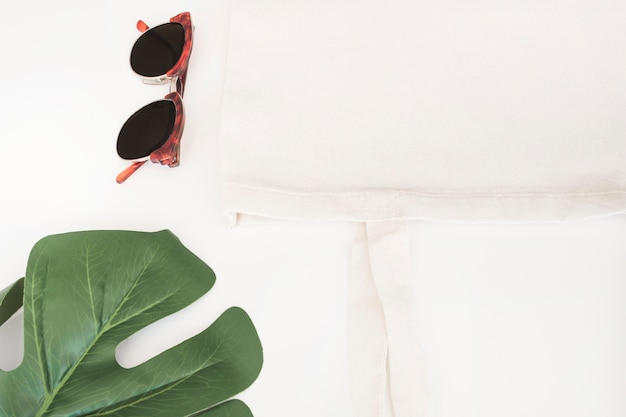 Sunglasses, white cloth bag and monstera leaf on white background Free Photo