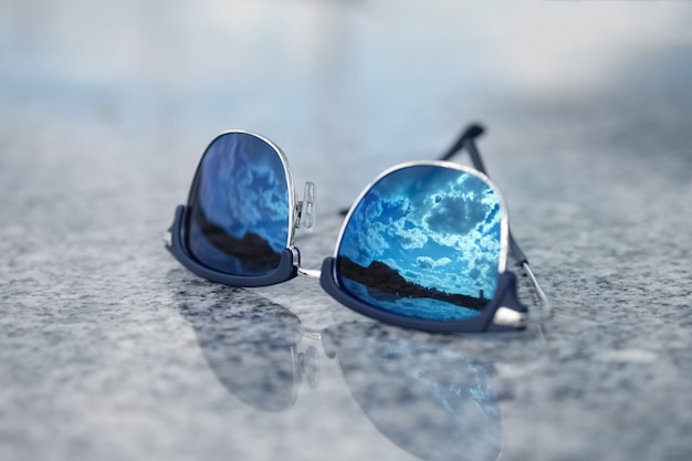 Sunglasses with reflection of the blue sky in glass. selective focus photo. Premium Photo