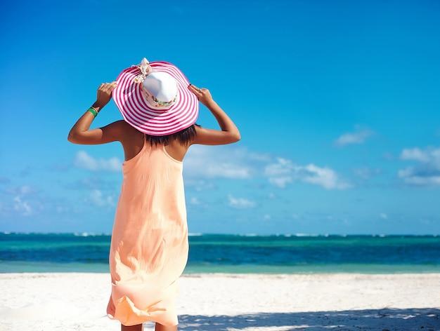 カラフルなsunhatと白い砂の上の夏の暑い日にビーチの海の近くを歩いてドレスのホット美しい女性 無料写真