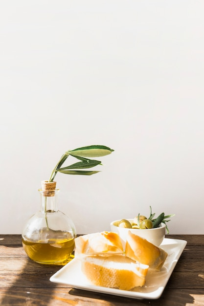 Sunlight falling on bread slice with olives in the bowl on the wooden desk Free Photo