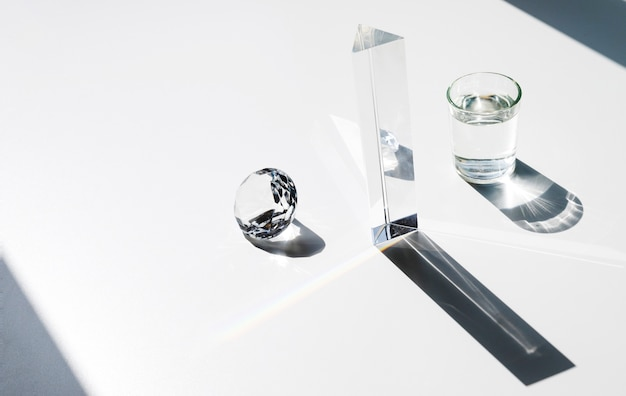 Sunlight falling on diamond; prism and water glass with shadow over white background Free Photo