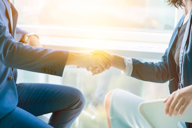 Sunlight falling on two businesspeople shaking hands Premium Photo