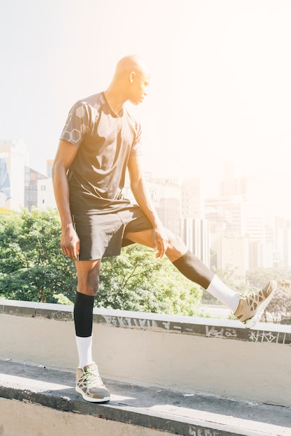 Sunlight over the male runner stretching legs overlooking the buildings in the city Free Photo