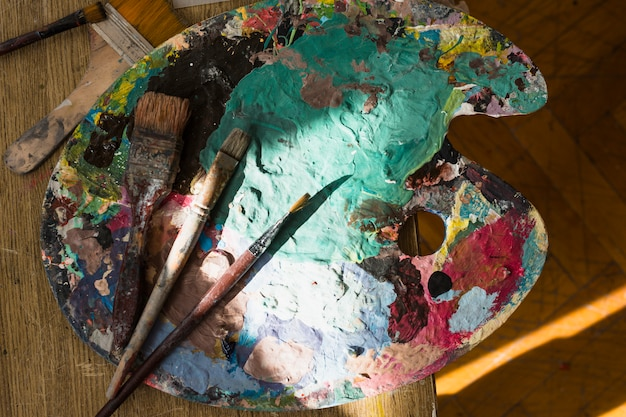 Sunlight on messy palette and brush over wooden table Free Photo