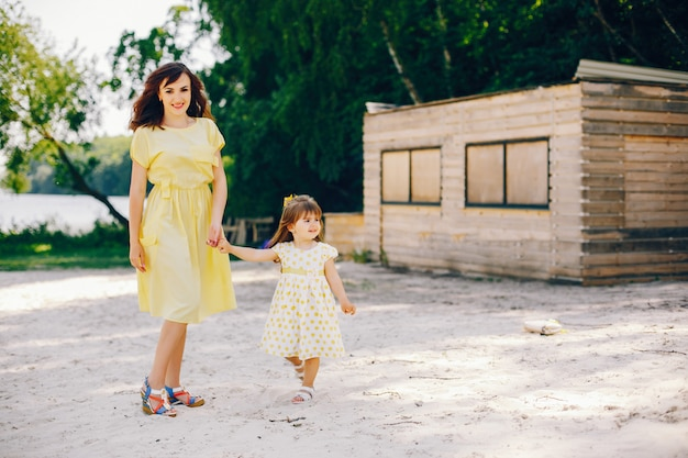 On a sunny beach with yellow sand, mom walks in a yellow dress and her little pretty girl Free Photo