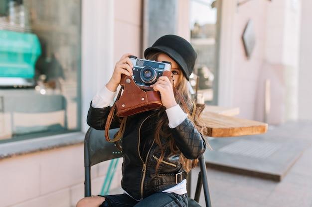 都会のカフェと笑顔で椅子に座っている幸せな少女の晴れた日。彼女はスタイリッシュな手でレトロなカメラを着ています。彼女はお母さん、本当の感情、良い気分を撮ります。 無料写真