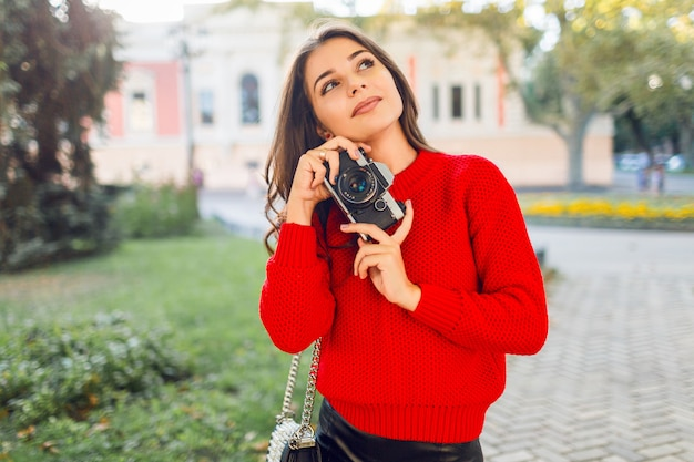 Sunny lifestyle image of pretty brunette girl in red casual pullover and skirt making pictures by photo camera in sunny park. walking in city garden and looking sightseens . Free Photo