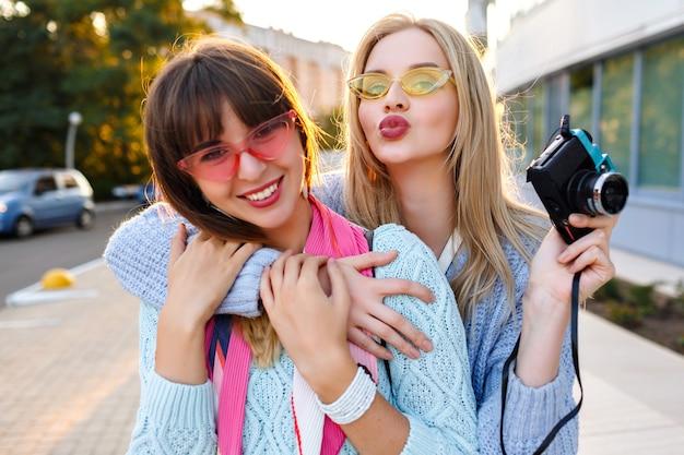 日当たりの良い屋外のポートレートまたは2つの陽気な面白い流行に敏感な女性パステルカラーの流行のセーターとメガネを着てビンテージカメラでselfieを作る、姉妹の親友が一緒に楽しんで。 無料写真