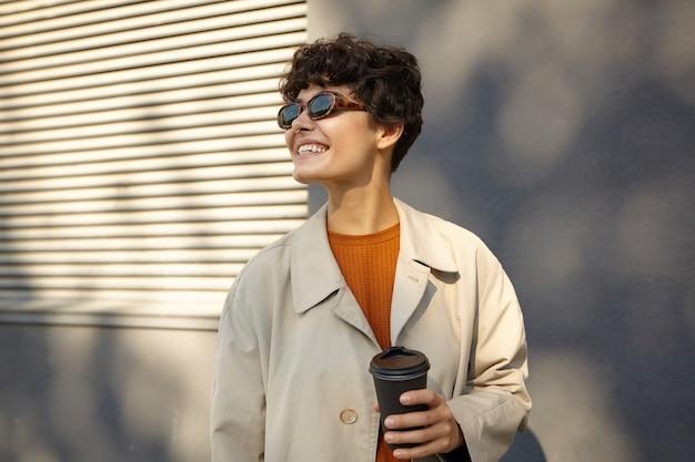 Солнечное фото симпатичной молодой кудрявой брюнетки с непринужденной прической, держащей черный бумажный стаканчик в поднятой руке и весело смотрящей в сторону с широкой улыбкой, одетой в модный наряд Бесплатные Фотографии