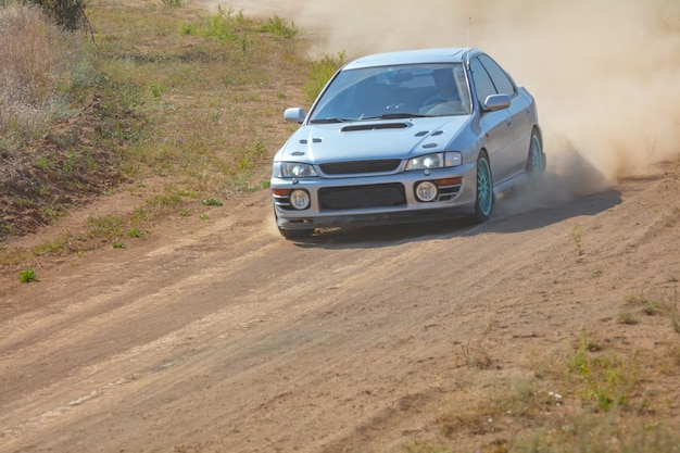Sunny summer day. dusty rally track. sports car does a lot of dust in turn 02 Premium Photo