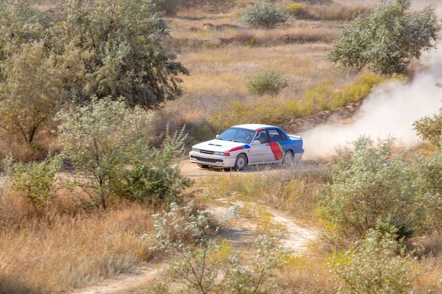 Sunny summer day. dusty rally track. sports car does a lot of dust in turn 04 Premium Photo