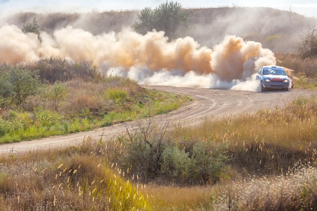 Sunny summer day. dusty rally track. sports car does a lot of dust in turn 05 Premium Photo