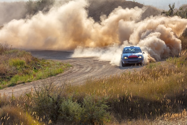 Sunny summer day. dusty rally track. sports car does a lot of dust in turn 06 Premium Photo