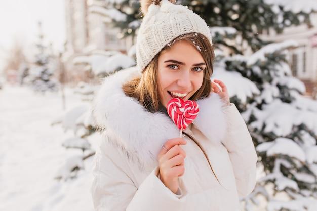 ピンクのロリポップをなめる魅力的な若い女性の通りの晴れた冬の朝。幸せな時間、暖かい白い服を着たきれいな女性の肯定的な感情、冬を楽しんでいるニット帽。 無料写真