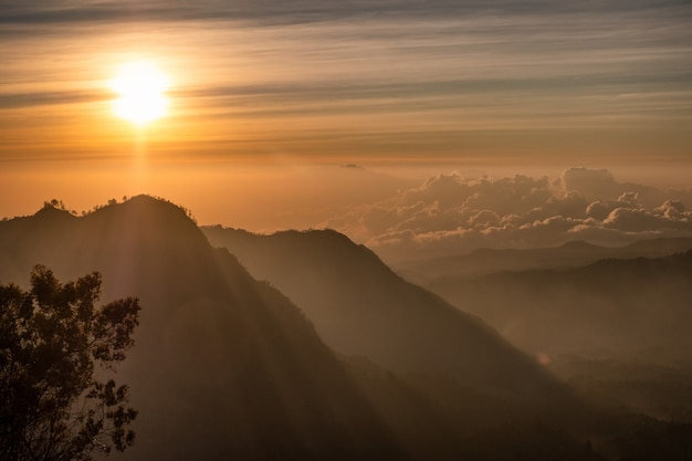 Sunrise over mountain with fog with village on hill Premium Photo