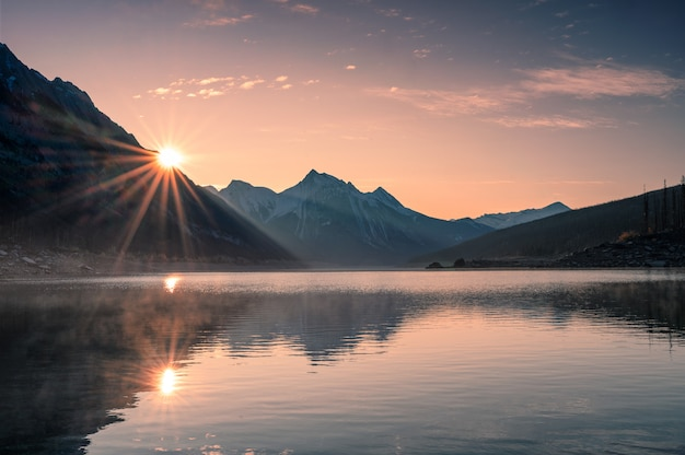 Sunrise on mountain with foggy in medicine lake at jasper Premium Photo