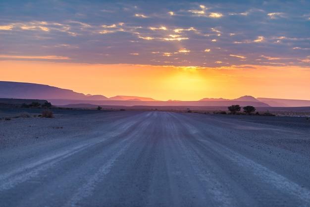 Sunrise over the namib desert, roadtrip in the wonderful namib naukluft national park, travel destination in namibia, africa. morning light, mist and fog, adventure off road. Premium Photo