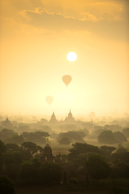 Sunrise scene hot air balloons fly over pagoda ancient city field in bagan myanmar. Premium Photo