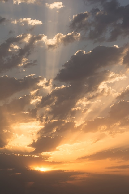Sunrise with dramatic dark clouds and light rays through clouds at sky Premium Photo