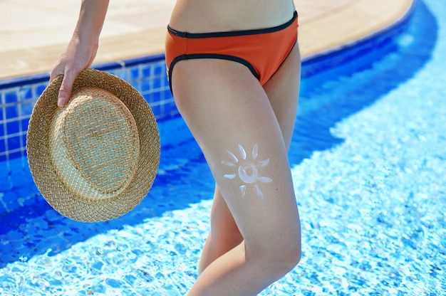 Sunscreen and beautiful female feet in the summer pool, the concept of protecting the skin Premium Photo