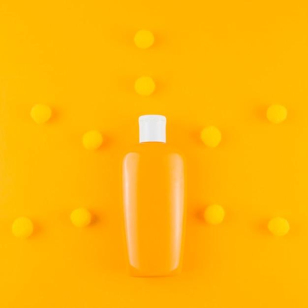 Sunscreen bottle with yarn pom pom ball on an orange backdrop Free Photo