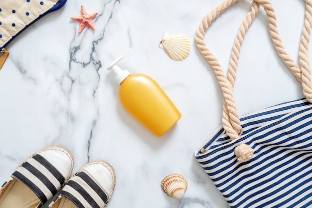 Sunscreen cream bottle, striped beach bag, seashells on marble background. Premium Photo