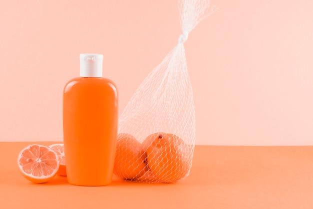 Sunscreen lotion bottle and grapefruits on colored backdrop Free Photo