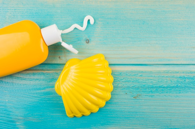 Sunscreen lotion bottle and plastic yellow scallop on turquoise wooden desk Free Photo