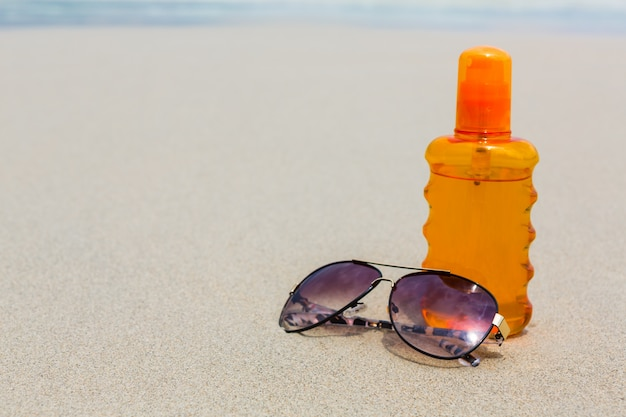 Sunscreen lotion and dark glasses on the beach for summer time Free Photo