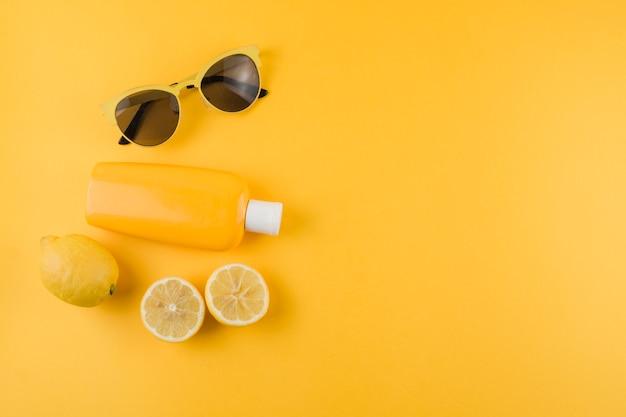 Sunscreen lotion; lemons and sunglasses on yellow background Free Photo