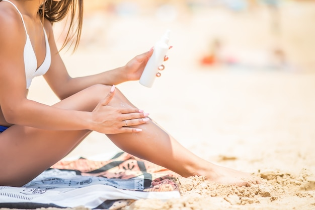 Sunscreen suntan lotion in spray bottle. young woman in spraying tanning oil on her leg from bottle. lady is massaging sunscreen lotion while sunbathing at beach. female model during summer vacation. Free Photo