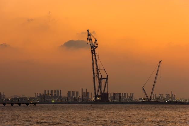 アラブ首長国連邦のドバイ港に沈む夕日。明るい空のクレーンのシルエット Premium写真