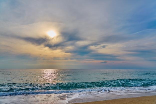 熱帯のビーチに沈む夕日、泡が砂に当たる波。 Premium写真