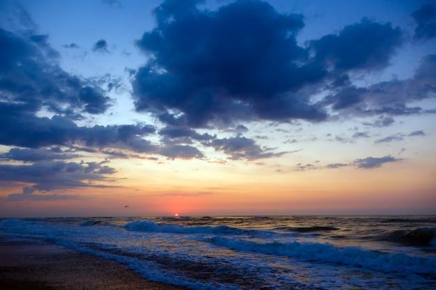 Sunset on a beach. stormy sea, cloudy sky. Premium Photo