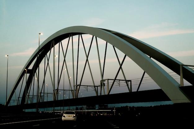 Sunset bridge over the road. Free Photo