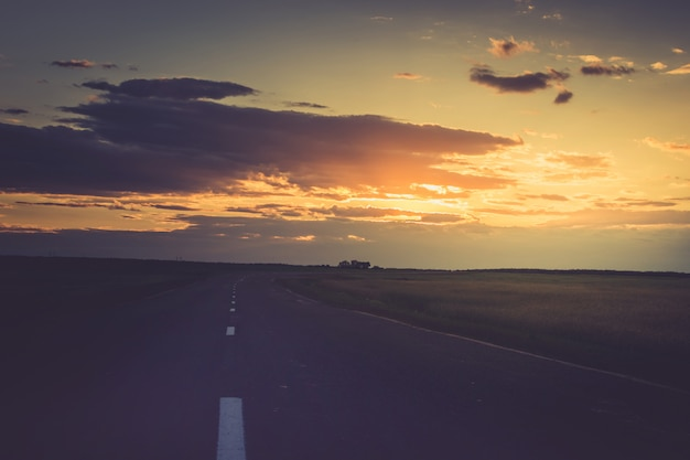 Sunset or a dawn over the road that goes into the distance. Premium Photo