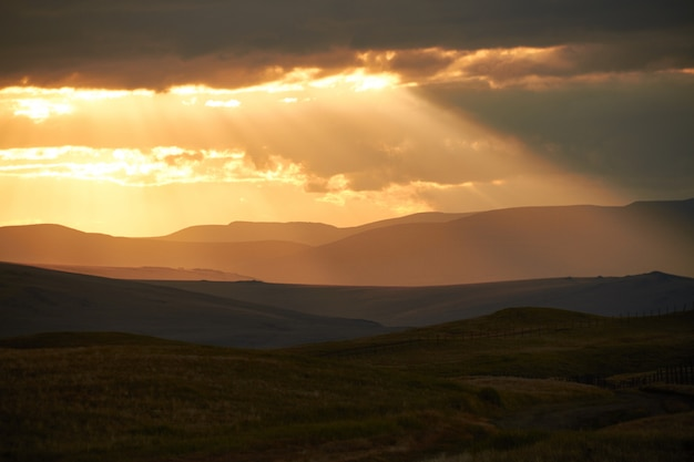 Sunset in the desert, the sun's rays shine through the clouds. ukok plateau of altai. fabulous cold landscapes Premium Photo