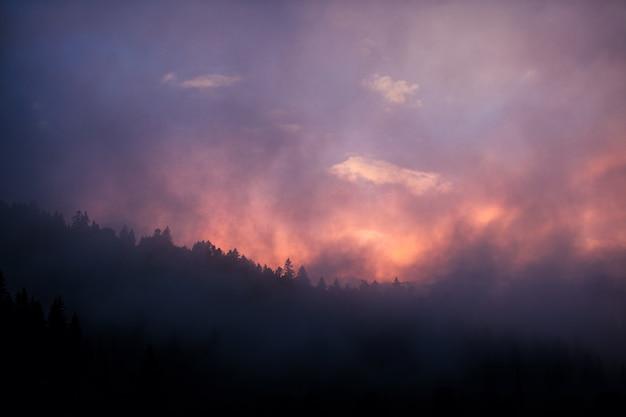 山に沈む夕日。場所ウクライナ、カルパティア。 Premium写真